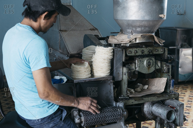 Chiapa de Corzo, Mexico - January 18, 2018: Man operating tortilla producing machinery