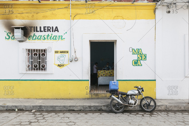 Chiapa de Corzo, Mexico - January 18, 2018: Motor bike parked outside bright storefront with people inside