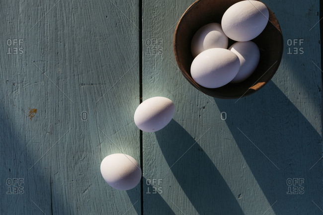 Top view of eggs on painted wooden table in late afternoon