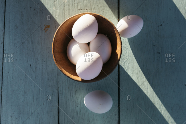 Fresh organic eggs in clay pot on shadowy picnic table from above