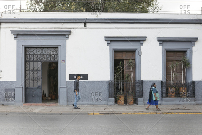 Oaxaca City, Mexico - January 24, 2018: Pedestrians walking past restaurant building