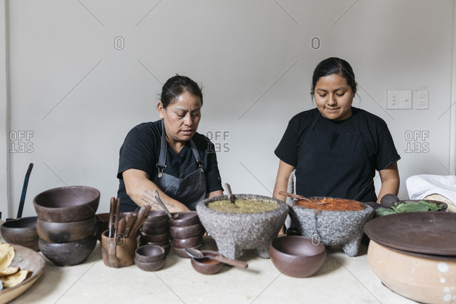 Oaxaca City, Mexico - January 25, 2018: Female restaurant cooks making large batches of fresh salsa