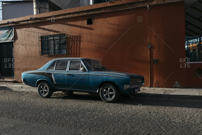 Oaxaca City, Mexico - January 25, 2018: Retro car parked next to warehouse in shadowy alley