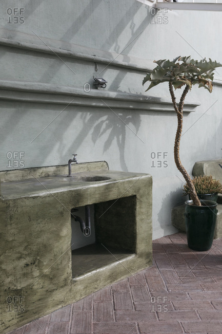 Outdoor marble slab counter and sink attached to building wall