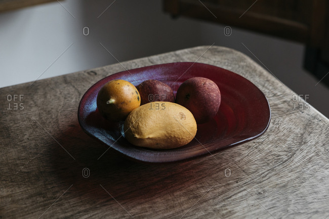 Ceramic bowl of fruit at corner of rustic wood table