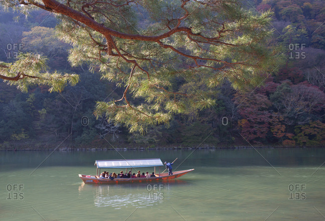 Arashiyama, Japan - November 28, 2015: Boat full of tourists travel along Oi river