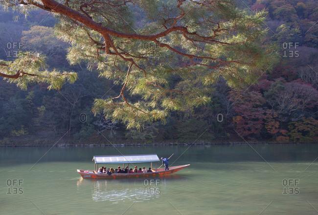 Arashiyama, Japan - November 28, 2015: Boat full of tourists travel along Oi river