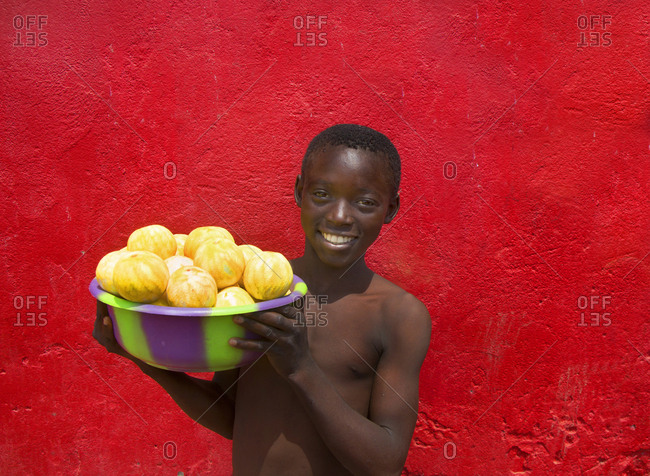 Sierra Leone, Africa - February 16, 2013: Portrait of young boy holding bucket of peeled oranges against bright red wall