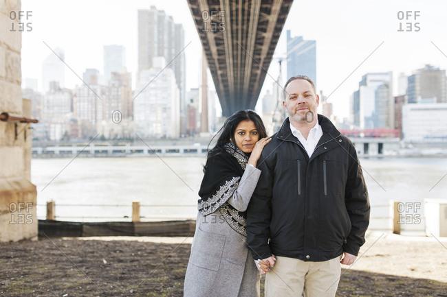 Mixed race couple standing under a bridge on Roosevelt Island
