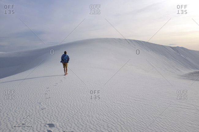 Man hiking alone at White Sands National Monument in New Mexico at sunset
