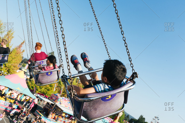 Rearview of young boy riding carousel at state fair