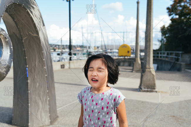 little girl of Chinese ethnicity with eyes closed while playing hide and seek in park