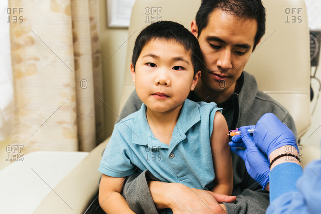 Dad holds onto son who remains impassive during injection