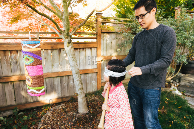 Father helps daughter put on blindfold before attacking pinata