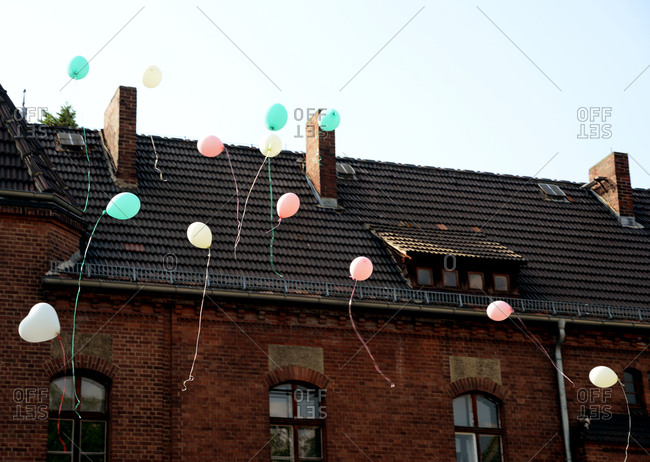 Balloons floating past the facade of a brick building