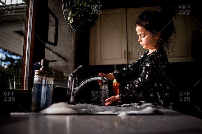 Young girl standing at kitchen sink checking temperature of water