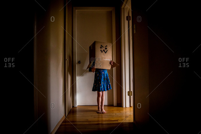 Young girl standing in passage wearing box with angry face on head