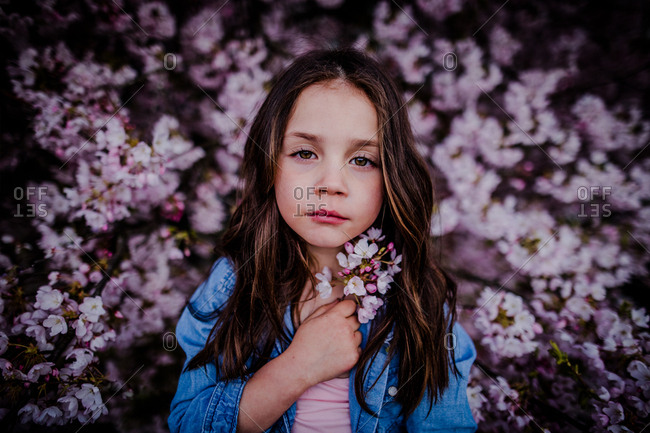 Moody portrait of young girl holding bunch of flowers against backdrop of blossoms