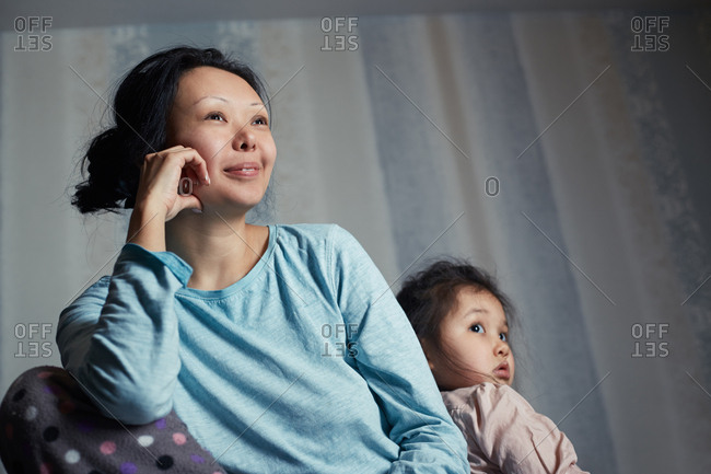 Mother and daughter sitting watching TV