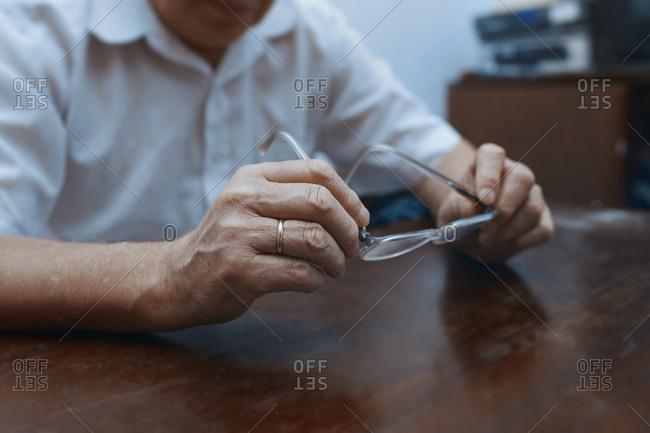 Senior man at home trying eyeglasses