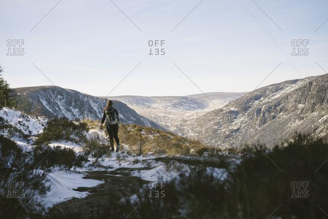 Female hiking thru Irish mountains in the sun and snow.