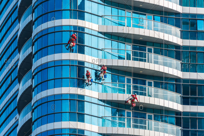 Abu Dhabi, United Arab Emirates - December 28, 2017: Window cleaners on skyscrapers of Abu Dhabi city