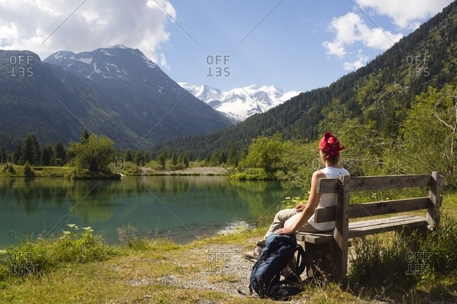 Pontresina, Engadine, Canton of Grisons, Switzerland, Europe - July 26, 2013: Hiker in the Val Morteratsch valley admiring the glacier and the Bernina mountain range