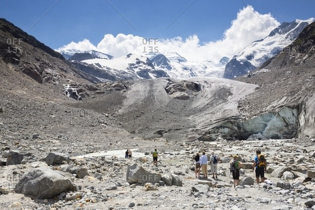 Pontresina, Engadine, Canton of Grisons, Switzerland, Europe - July 26, 2013: Tourists admiring the Morteratsch Glacier in Val Morteratsh with Bernina mountain group in the background