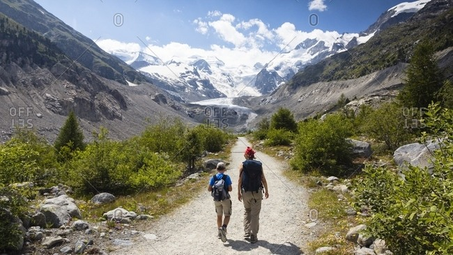 Pontresina, Engadine, Canton of Grisons, Switzerland, Europe - July 26, 2013: Hiking in Val Morteratsch valley, in the background the glacier and the Bernina mountain range
