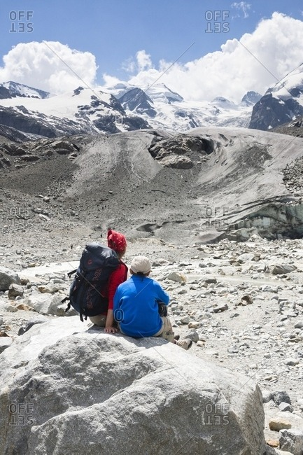 Pontresina, Engadine, Canton of Grisons, Switzerland, Europe - July 26, 2013: Hikers in Val Morteratsch valley, in the background the glacier and the Bernina mountain range