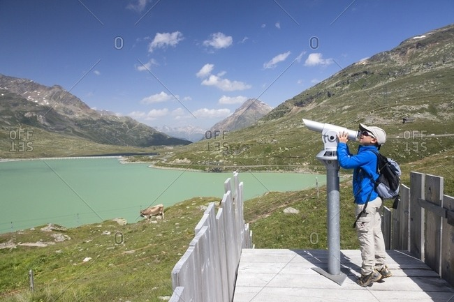 Engadin, Canton of Grisons, Switzerland, Europe - July 28, 2013: Child looking the Bernina mountain group with coin operated binoculars, Bernina Pass, in the background the Lago Bianco lake