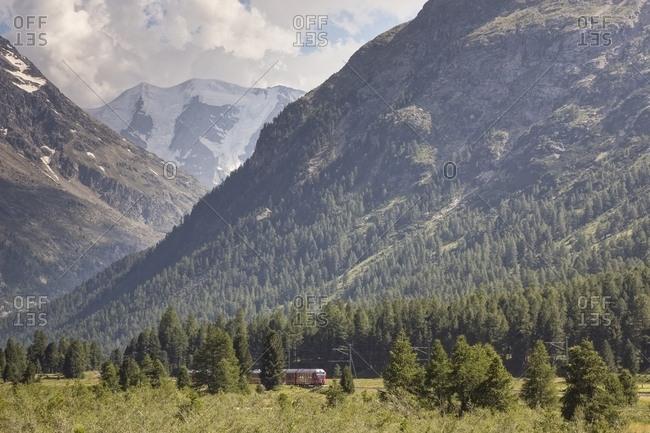 Bernina Express train from Tirano to Saint Moritz, in the background Morteratsch glacier and Bernina mountain range, Pontresina, Engadin, Canton of Grisons, Switzerland, Europe