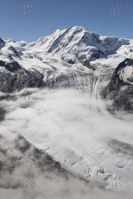View from Gornergrat mountain towards Monte Rosa or Breithorn mountain range with Liskamm and Gorner Glacier in the clouds, Zermatt, Valais, Switzerland, Europe