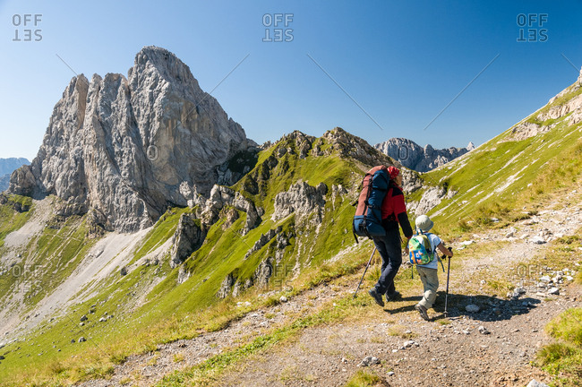 Mother and child walking in Sesis valley, in the background the Pic Chiadenis mount, Sappada, dolomites, Friuli Venezia Giulia, Italy, Europe