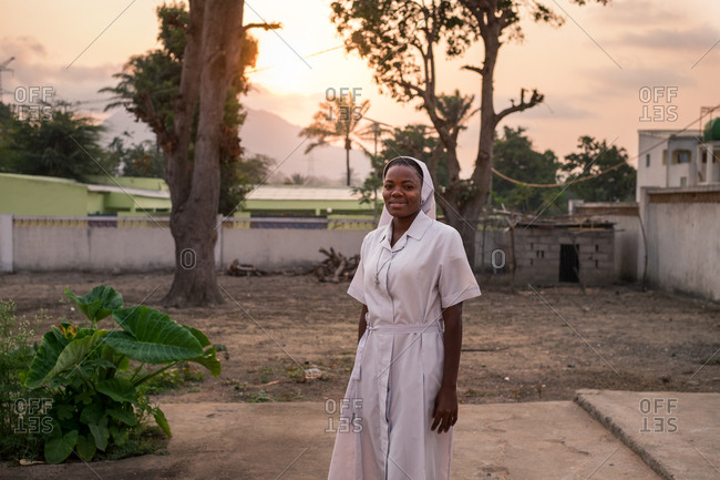 Angola, Africa - April 5, 2018: Smiling ethnic nurse in sunny evening