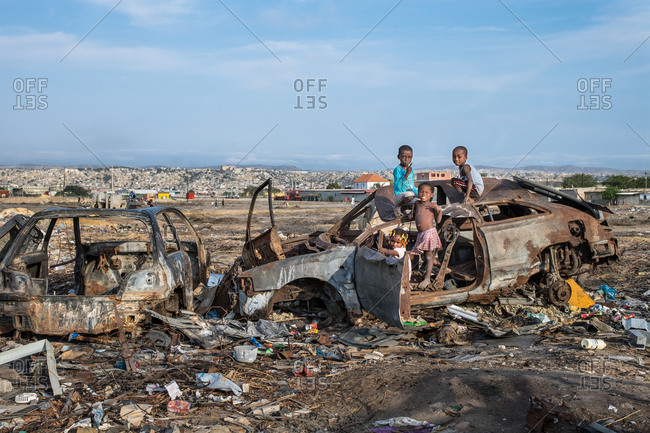 Angola, Africa - April 5, 2018: African children standing and playing on grungy car on the dump