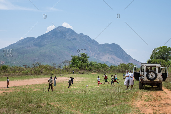 Angola, Africa - April 5, 2018: African children running on green meadow and playing football