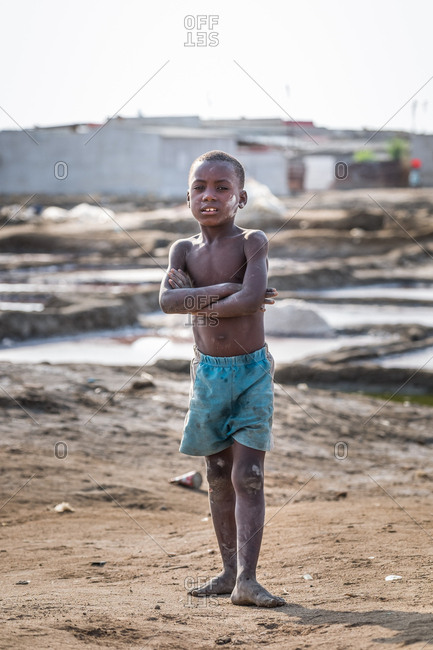 Angola, Africa - April 5, 2018: Young little African boy standing with arms crossed and looking at camera