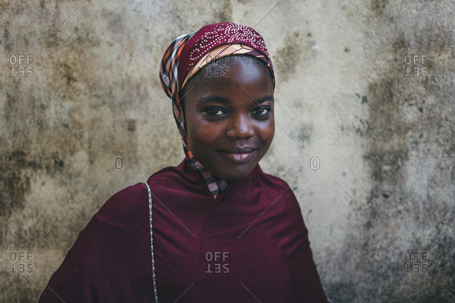 Cameroon, Africa - April 5, 2018: Pretty African woman in red traditional clothes standing at rough wall and looking at camera
