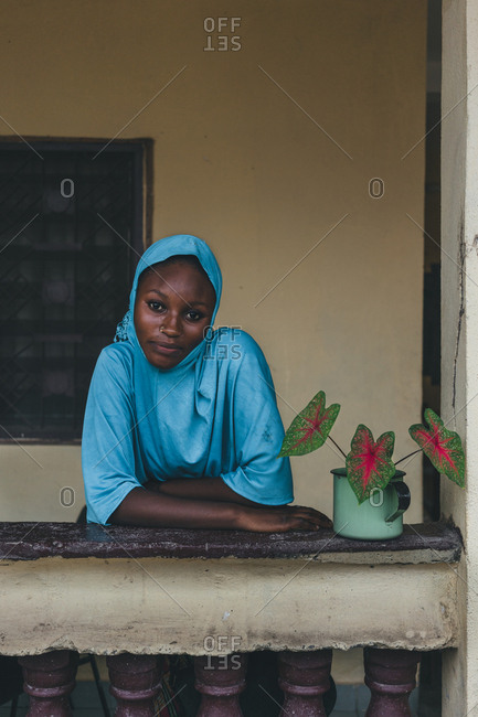 Cameroon, Africa - April 5, 2018: Pretty young African woman in blue traditional clothes leaning on handrail and looking at camera