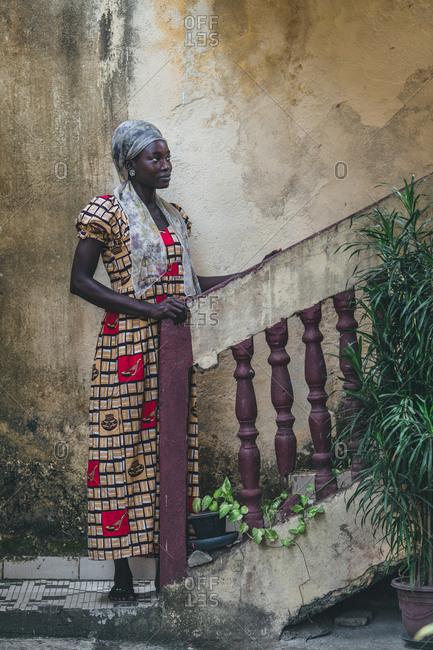 Cameroon, Africa - April 5, 2018: Thoughtful young ethnic woman standing at stairs and looking away