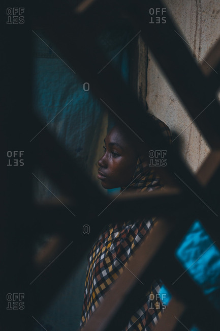 Cameroon, Africa - April 5, 2018: Thoughtful young ethnic woman standing at the wall and looking away