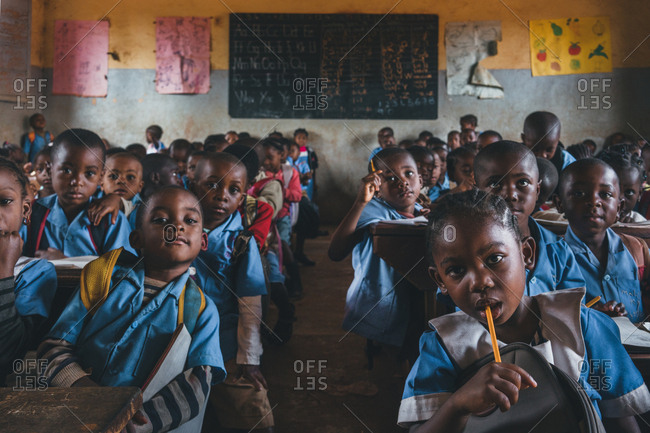 Cameroon, Africa - April 5, 2018: Group of African pupils sitting with pencils in the class and looking at camera