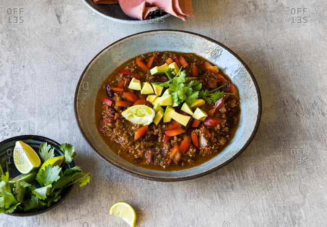 Bowl of beef chili with avocado and lime