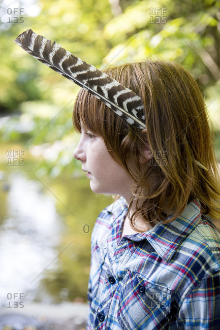 Closeup of boy with feather in hair looking away while standing at forest