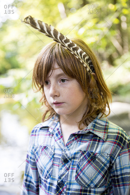 Closeup of thoughtful boy with feather in hair looking away while standing at forest