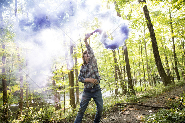 Preteen boy waving purple smoke bomb in forest