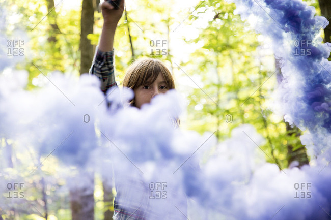 Portrait of preteen boy holding purple flare in forest