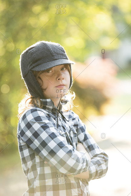Portrait of confident boy with arms crossed wearing hat