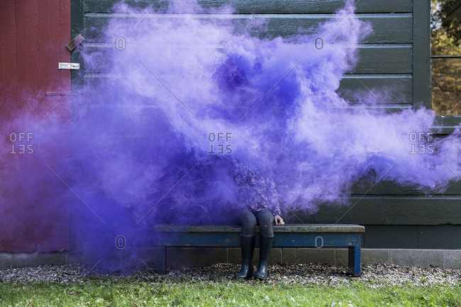 Young girl surrounded by purple smoke while sitting on bench outside house